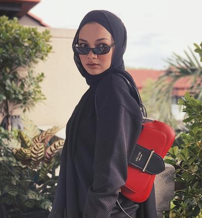 3. Prada Sidonie Merah dengan Outfit Serba Hitam ala Noor Neelofa