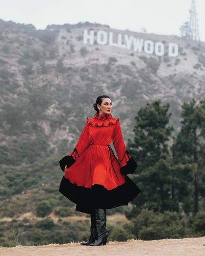 Gaya Candid dengan Dress Merah Hitam Berlatarkan Hollywood
