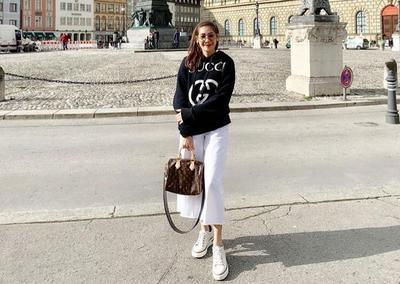 Branded hoodie, white pants, dan sneakers