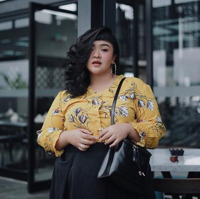 Kombinasi rok hitam dengan atasan berwarna mustard dengan corak bunga, membuat wajah Tira menjadi lebih cerah ya Ladies.